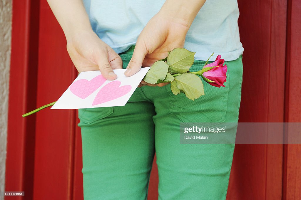 Guy with a love letter & rose outside a red door : Stock Photo