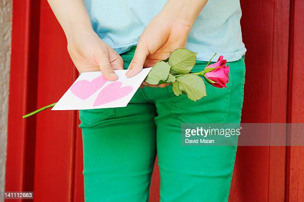 Guy with a love letter & rose outside a red door