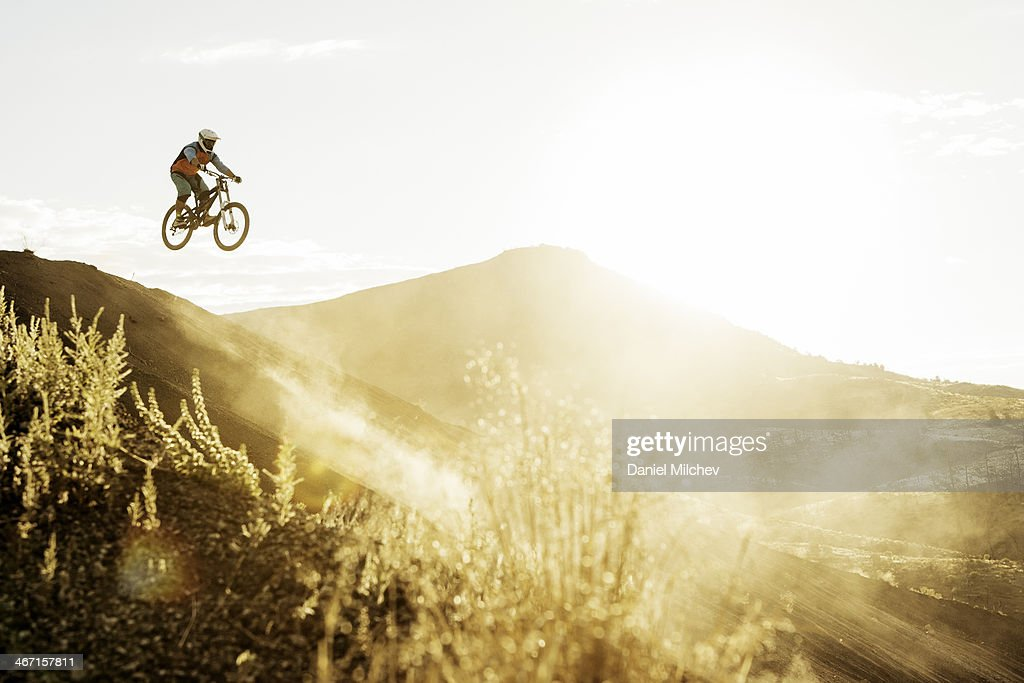 Guy with a mountain bike jumping in to the sun. : Stock Photo
