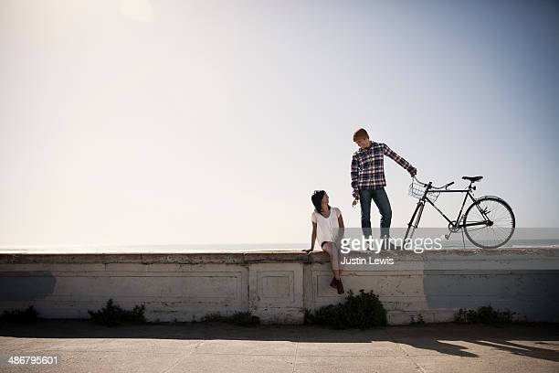 Guy with bike on cement wall by beach with a girl