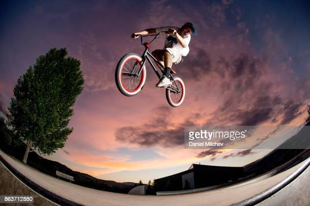 Guy with bmx jumping at a skatepark at dusk.