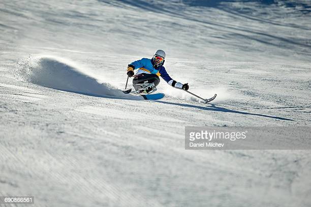 guy with differing abilitie skiing down a ski run. - スキー板 ストックフォトと画像