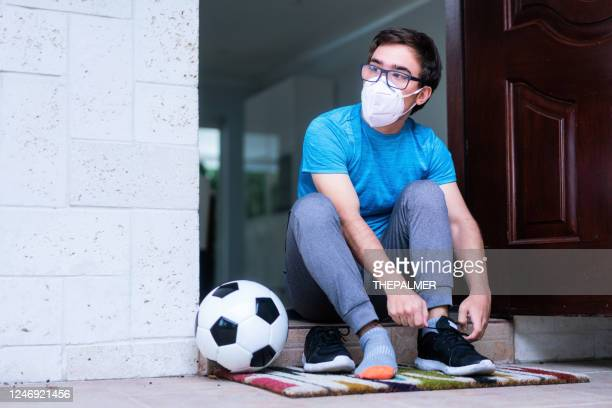 guy with face mask putting on shoes to go an play some soccer - football face mask stock pictures, royalty-free photos & images