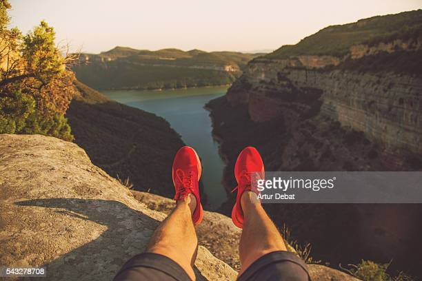 Guy with red shoes over a stunning rock pulpit formation taken pictures from personal point of view with the landscape and lake with vertical rock formations on sunset in the Catalonia region.