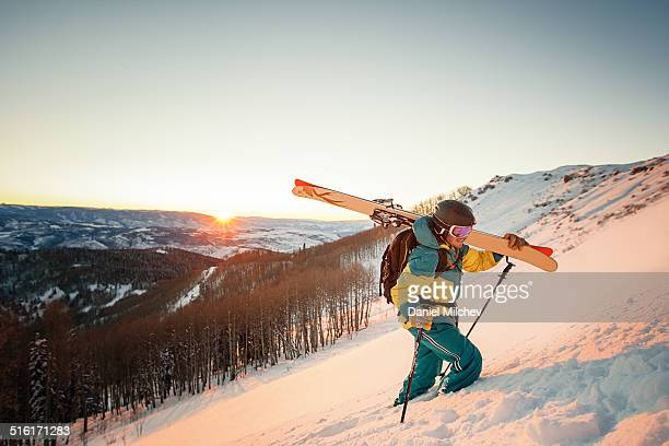 Guy with skis hiking during sunset in Colorado.
