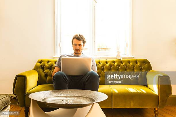 Guy working on laptop indoor sitting on a sofa
