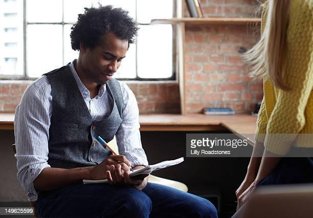 Guy writing notes while girl explains an idea