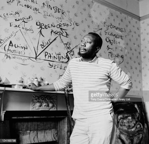 Guyana born British artist Frank Bowling in a studio, London, 1962. Elements of his art theory are painted on the wall behind him.