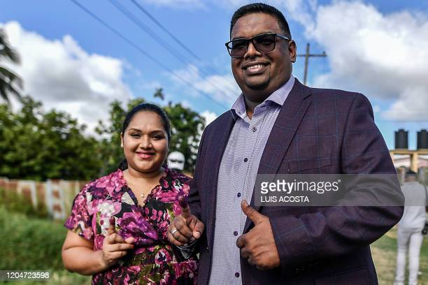Guyana's presidential candidate for the opposition leftist People's Progressive Party Mohamed Irfaan Ali and his wife Arya Ali show their...
