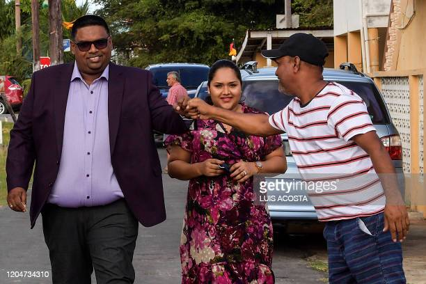 Guyana's presidential candidate for the People's Progressive Party Mohamed Irfaan Ali accompanied by his wife Arya Ali greets a supporter after...