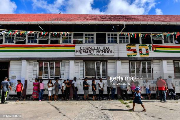 Guyanese citizens line up to vote in Leonora Guyana on March 2 2020 Voters in Guyana began casting ballots Monday in a general election to decide...