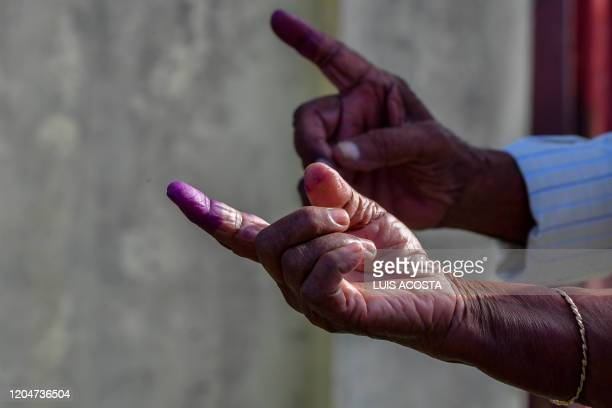Guyanese citizens show their inked fingers after voting in Leonora Guyana on March 2 2020 Voters in Guyana began casting ballots Monday in a general...