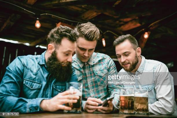 Jungs von Pub trinken Bier und Smartphone betrachten