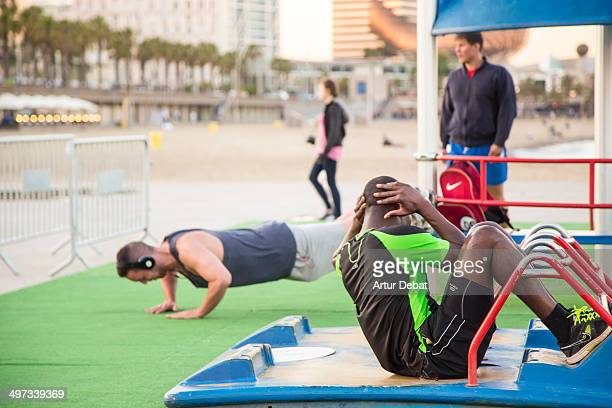 Guys doing push ups and abdominal crunch on Crossfit routine in a open outside gym