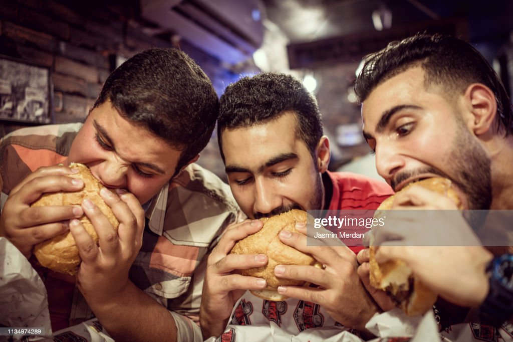 Guys eating burgers : Stock Photo