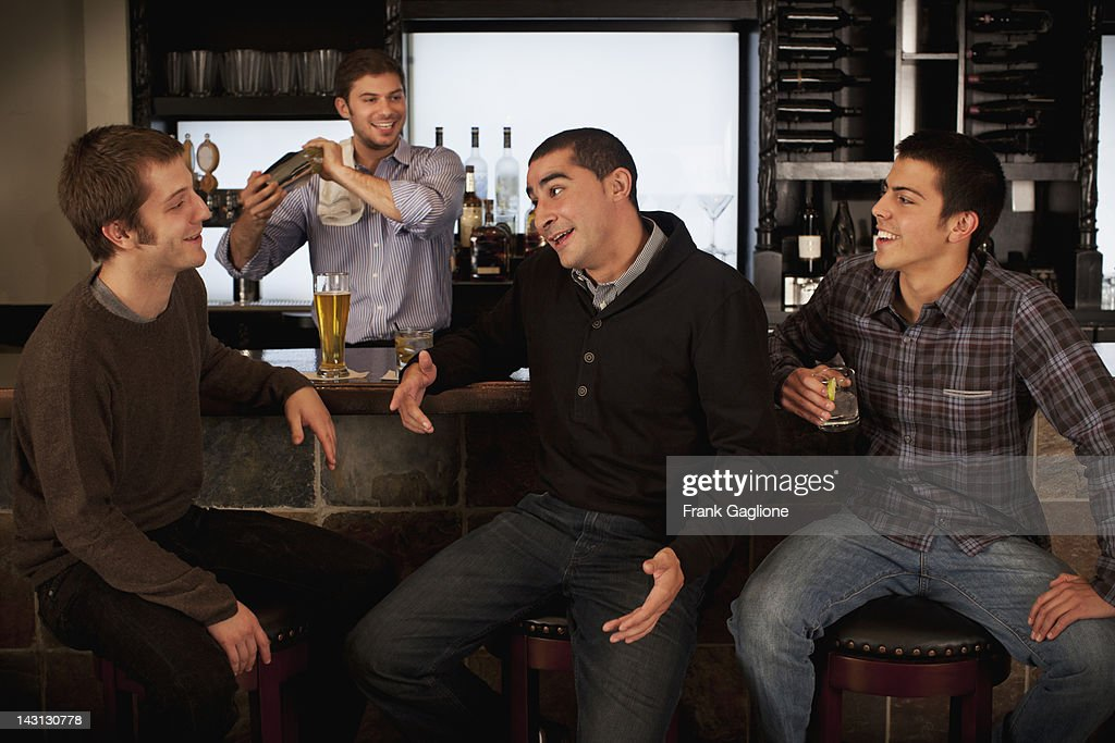 Guys hanging out at a bar. : Foto de stock