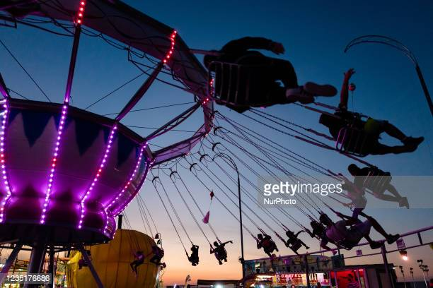 Guys have fun catching the plume in the Catene carousel in the funfair at Secca dei Pali in Molfetta on the occasion of the Patronal Festival on 10...