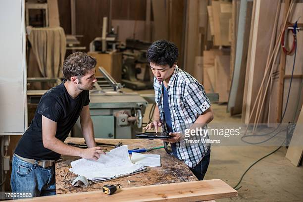2 guys looking at plans in a workshop