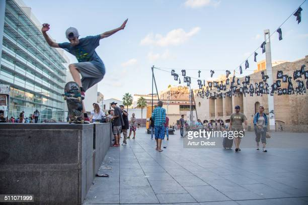Guys practicing skateboard in the streets of Barcelona city in the MACBA museum using the street furniture like a skatepark