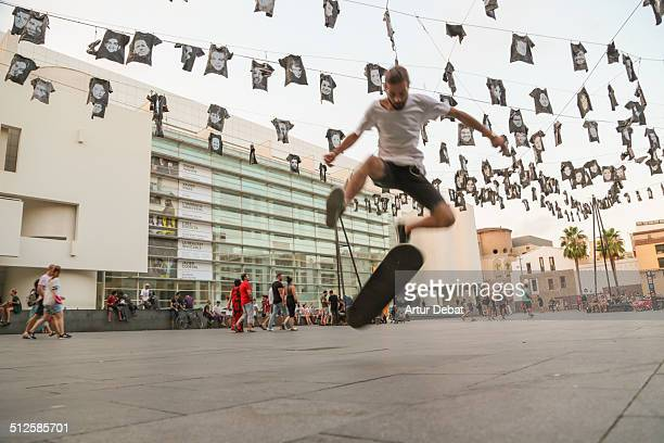 Guys practicing skateboarding and doing tricks in the streets of Barcelona city in the MACBA square museum Catalonia Europe