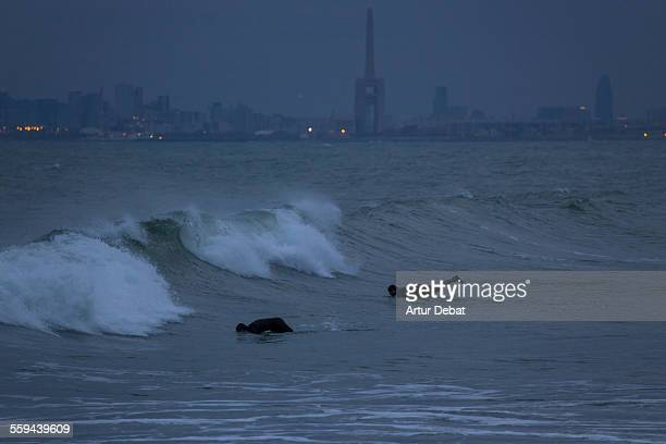 Guys practicing surf at dusk in the Barcelona's shoreline during the spring storms with the city lights on background Masnou Catalonia Europe