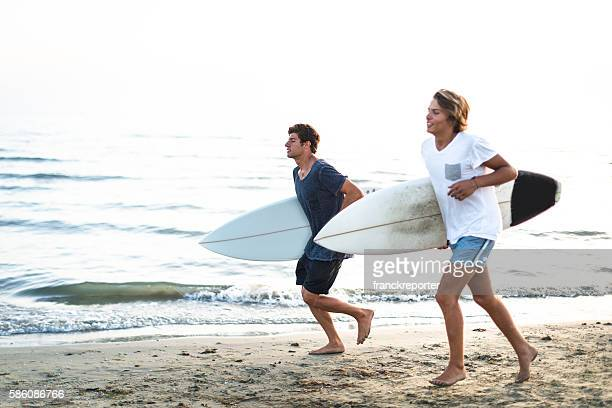 guys running on the beach with surfboard