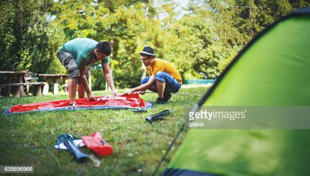 Guys setting up a camping tent.
