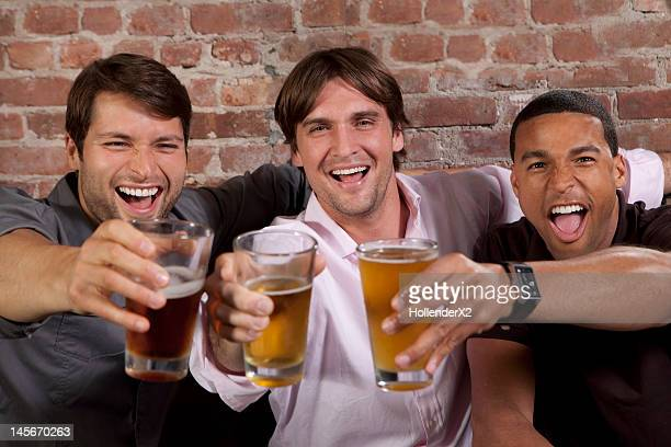 guys toasting to the camera with their beers