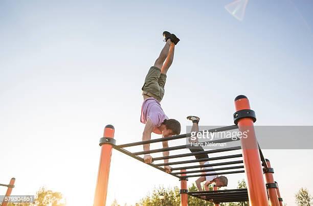 Guys training in park on monkey bars