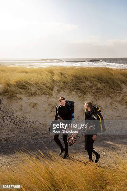 guys with kitesurf equipment walking by beach - robin skjoldborg stock pictures, royalty-free photos & images