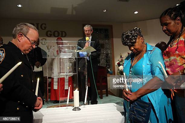 Gwen Carr mother of Eric Garner and his widow Esaw Garner stand with Staten Island Borough Commander Chief Edward Delatorre in a joint candle...