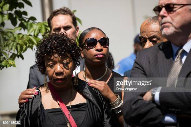 Gwen Carr mother of the late Eric Garner is consoled by Ellisha Garner during a press conference after meeting with Department of Justice officials...