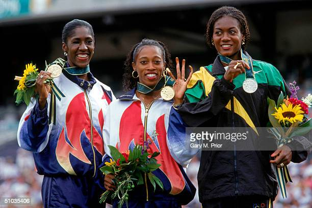 Gwen Torrence 3rd Place Gail Devers 1st Place and Merlene Ottey 2nd Place smile at the podium displaying their medals during the medals ceremony...