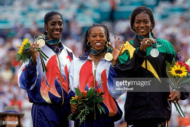 Gwen Torrence , 3rd Place, Gail Devers , 1st Place, and Merlene Ottey , 2nd Place, smile at the podium displaying their medals during the medals...