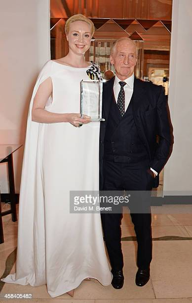 Gwendoline Christie winner of the British Actress of the Year award and presenter Charles Dance pose at the Harper's Bazaar Women Of The Year awards...