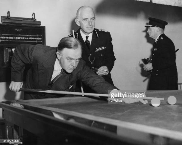 Gwilym Lloyd George , the Home Secretary, tries out a billiards table after opening the new police headquarters of Number 1 District on Earl's Court...
