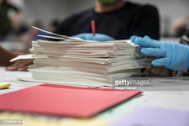 Gwinnett County election workers handle ballots as part of the recount for the 2020 presidential election at the Beauty P. Baldwin Voter...