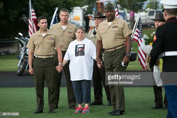 Gy Sgt Joe Ingram holds the hand of Cathy Wells mother of Lance Cpl Skip Wells as she is presented flowers by Marines during a memorial held for...