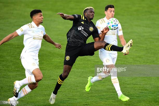 Gyasi Zardes of Columbus Crew controls the ball past Miles Robinson and Fernando Meza of Atlanta United during the second half of their game at...