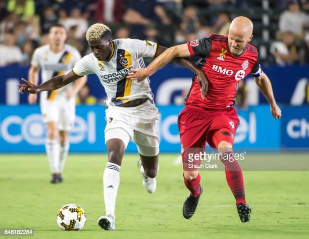 Gyasi Zardes of Los Angeles Galaxy battles Michael Bradley of Toronto FC during the Los Angeles Galaxy's MLS match against Toronto FC at the StubHub...