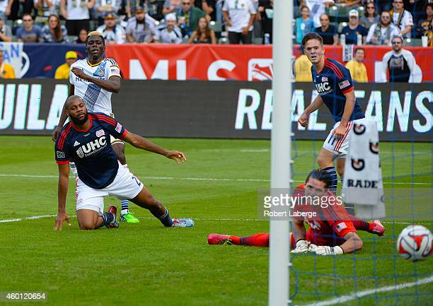 Gyasi Zardes of the Los Angeles Galaxy scores on goalie Bobby Shuttleworth of the New England Revolution as Andrew Farrell and Kelyn Rowe of the...