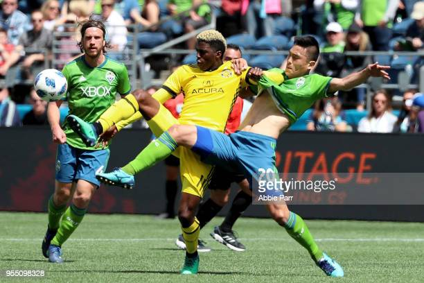 Gyasi Zerdes of Columbus Crew fights for the ball against Kim Keehee of the Seattle Sounders during their game at CenturyLink Field on May 5 2018 in...