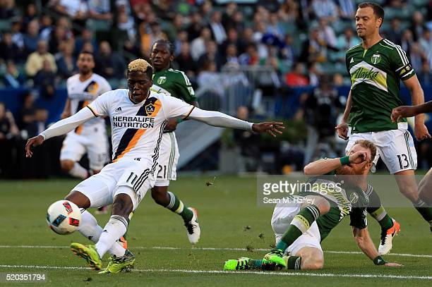 Gyasi Zerdes of Los Angeles Galaxy kicks the ball as Nat Borchers and Jack Jewsbury of Portland Timbers pursue him during the first half of their MLS...