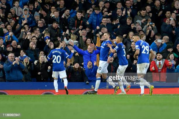Gylfi Sigurdsson of Everton celebrates his goal with Bernard and Richarlison during the Premier League match between Everton and Chelsea at Goodison...