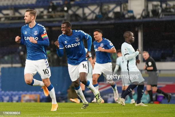 Gylfi Sigurdsson of Everton celebrates with teammates Abdoulaye Doucoure and Allan after scoring their team's first goal from the penalty spot during...