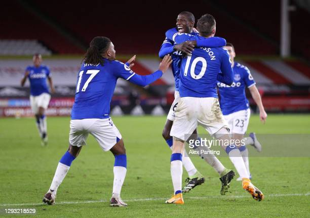 Gylfi Sigurdsson of Everton celebrates with teammates Alex Iwobi and Abdoulaye Doucoure after scoring his team's first goal during the Premier League...