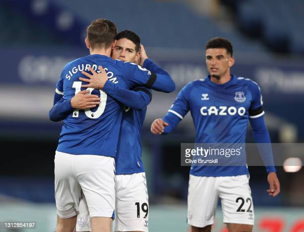 Gylfi Sigurdsson of Everton celebrates with teammates James Rodriguez and Ben Godfrey after scoring their team's first goal from the penalty spot...