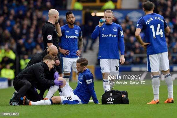 Gylfi Sigurdsson of Everton is treated for a knee injury by the Everton medical team during the Premier League match between Everton and Brighton and...