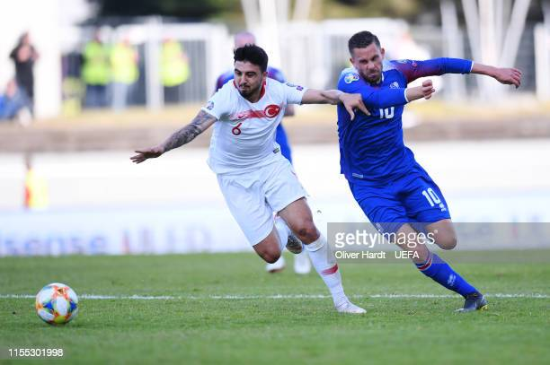 Gylfi Sigurdsson of Iceland challenges for the ball with Ozan Tufan of Turkey during the UEFA Euro 2020 Qualifier match between Iceland and Turkey at...