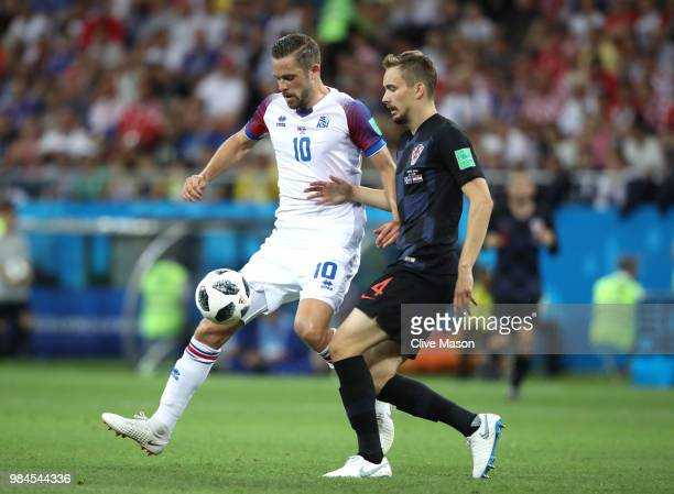 Gylfi Sigurdsson of Iceland is challenged by Filip Bradaric of Croatia during the 2018 FIFA World Cup Russia group D match between Iceland and...